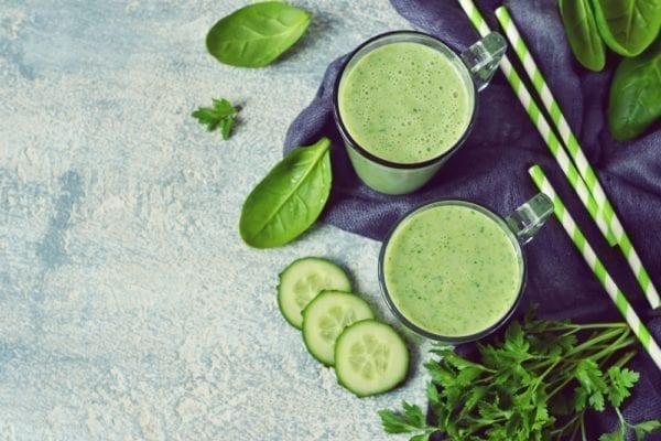 Vier Zutaten für den perfekten grünen Smoothie: zwei fertige Smoothies im Glas