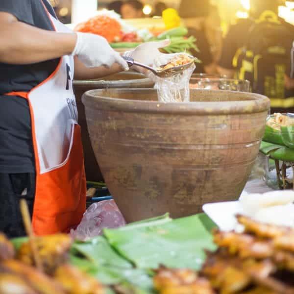 Der authentische Papayasalat Som Tam wird in riesigen Tonmörsern zubereitet