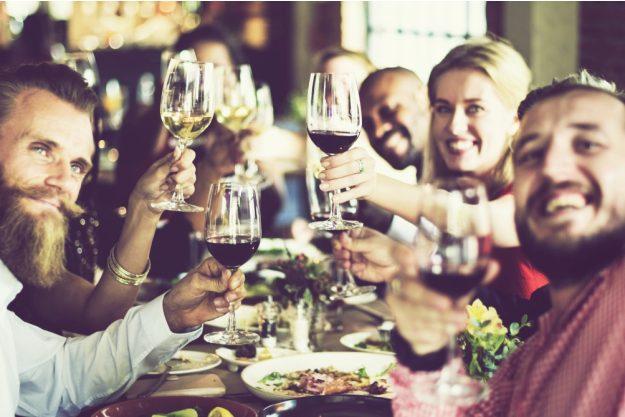 Kulinarisches Firmenevent – Lachende Kursteilnehmer stoßen mit Wein an