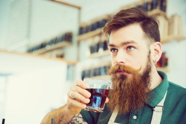Barista-Kurs-Gutschein –Mann mit Bart riecht an Kaffee