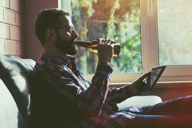 Online Bierverkostung – Mann trinkt Bier zuhause