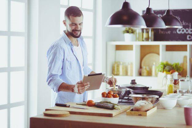 Online Kochkurs –  Mann kocht zuhause mit Tablet