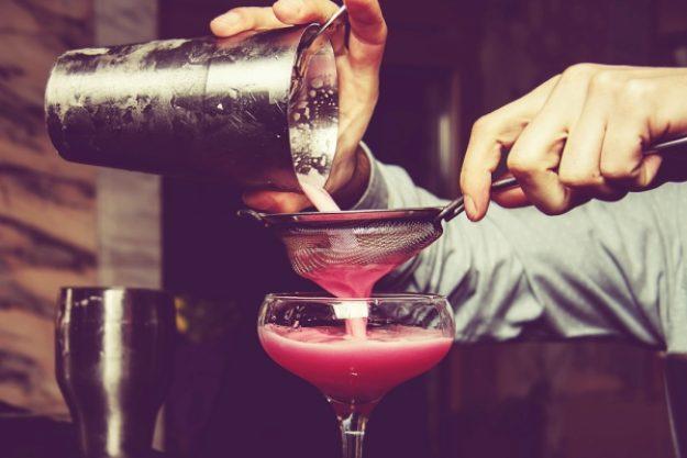Cocktailkurs-Gutschein –Mann siebt pinken Cocktail
