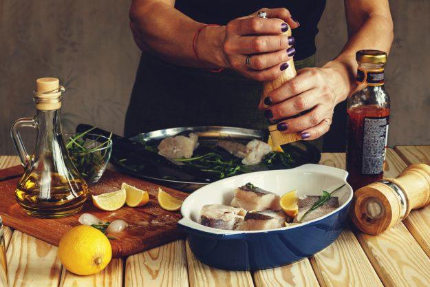 Fisch-Kochkurs München - Frau würzt Fisch