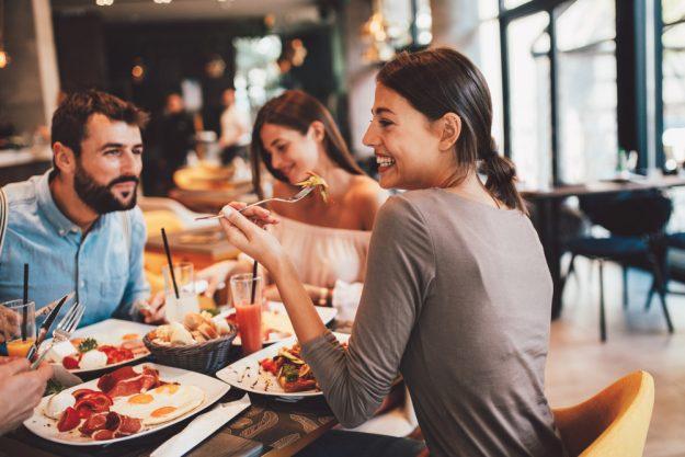Kulinarische Stadtführung Düsseldorf – Frau isst mit Freunden